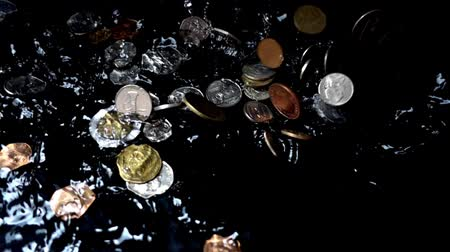 centavo : Coins fall in water. Slow motion. Stock Footage
