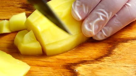 placa de corte : Cook cuts potatoes on a cutting board.