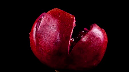 ve slupce : Pomegranate on a black background. Shooting on a black background. Dostupné videozáznamy
