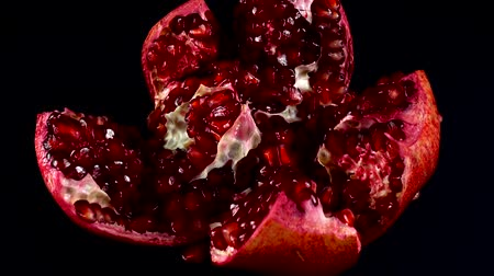 皮が付いたままの : Pomegranate on a black background.