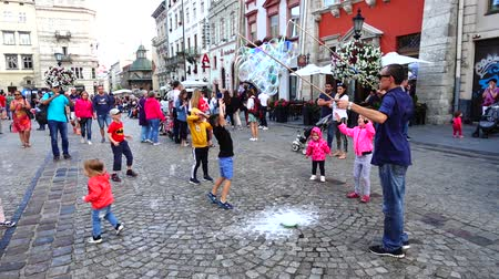 lviv : LVIV, UKRAINE - AUGUST 3, 2019: The unknown man lets soap bubbles for children to squares of the city. Slow motion.