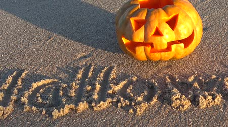 jack olantern : Spooky halloween pumpkin. Inscription Halloween on sand of the sea beach. Stock Footage