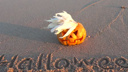 homály : Spooky halloween pumpkin. Inscription Halloween on sand of the sea beach. Stock mozgókép