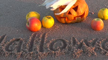 pigwa : Spooky halloween pumpkin. Inscription Halloween on sand of the sea beach. Wideo