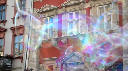 europeu : The artist sprays bubbles in the central square of the city.