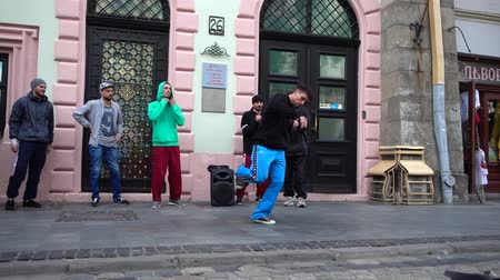hiphop : LVIV, UKRAINE - AUGUST 28, 2019: Unknown guys dance break on the street of the city. Slow motion.