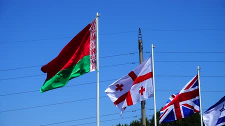 labor union : Flags of Belarus, Georgia, Great Britain and Israel on flagpoles.