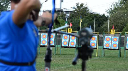 aimed : Archers aim and shoot at targets.