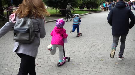 parky : LVIV, UKRAINE - SEPTEMBER 21, 2019: Children s cycling in the city park. Slow motion.