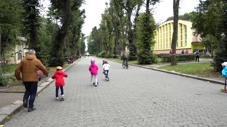 wrzesień : LVIV, UKRAINE - SEPTEMBER 21, 2019: Children s cycling in the city park. Slow motion.