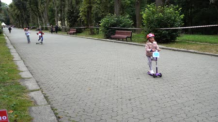 bisikletçi : LVIV, UKRAINE - SEPTEMBER 21, 2019: Children s cycling in the city park. Slow motion.