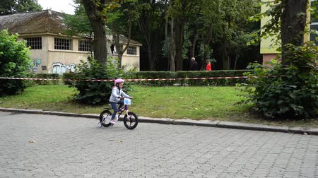 mond : LVIV, UKRAINE - SEPTEMBER 21, 2019: Children s cycling in the city park. Slow motion.