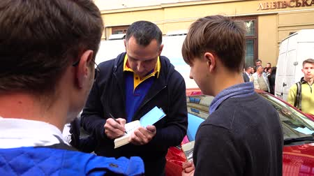 political prisoner : LVIV, UKRAINE - SEPTEMBER 22, 2019: Former Kremlin prisoner Oleg Sentsov gives autographs to people.