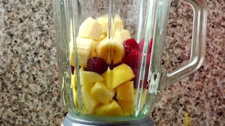 harmanlanmış : Filling in the blender of apples, raspberry and bananas. Preparation of smoothie in the blender.