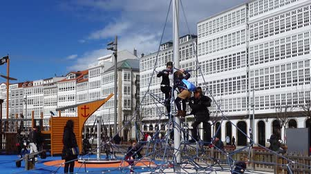 bank : LA CORU A, SPAIN - APRIL 2, 2018: Children at the playground on the city embankment. La Coru a the large city in the northwest of Spain, the resort and the port.