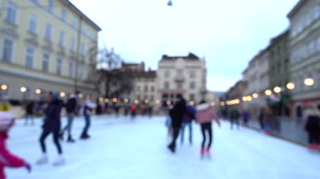 ice skating : Unknown people skate in the square of the city. Out of focus. Stock Footage