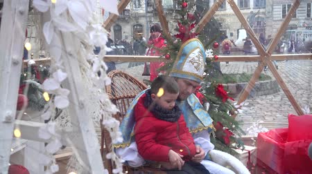 záradék : LVIV, UKRAINE - DECEMBER 15, 2019: Christmas meetings of children with St. Nicholas in the square of the city. Stock mozgókép