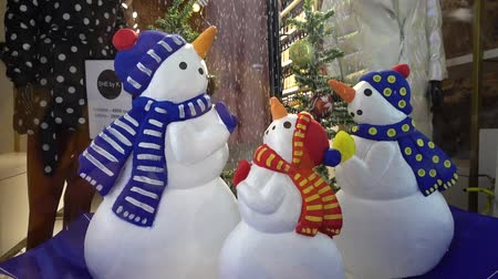 продавать : LVIV, UKRAINE - DECEMBER 15, 2019: New Years decoration of the shop window. Snowmen in an inverted umbrella.