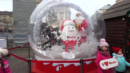 Навидад : LVIV, UKRAINE - DECEMBER 21, 2019: Christmas presents from kinder surprise in the city square. Christmas ball with Christmas tree, snow and gifts. Стоковые видеозаписи