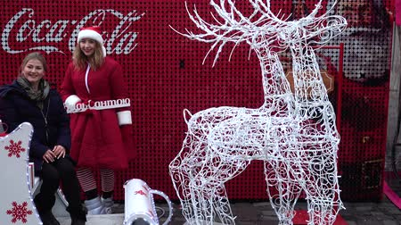 そり : LVIV, UKRAINE - DECEMBER 21, 2019: Unknown people are photographed with deer and sleigh against the background of Coca-Cola Christmas advertisement.