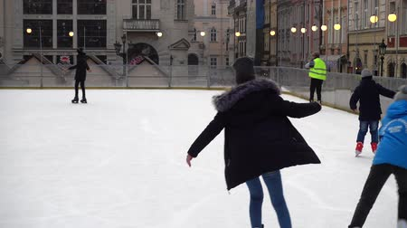 ice skating : LVIV, UKRAINE - DECEMBER 21, 2019: Unknown people skate in the square of the city.