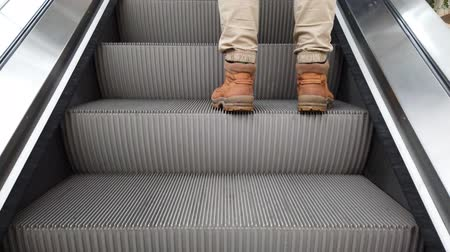 buty : Movement of the escalator. The man walks up the escalator.