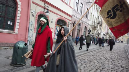 nobreza : LVIV, UKRAINE - JANUARY 7, 2020: Unknown people in medieval clothes walk down the street of the city. Restaurant advertising in medieval style.