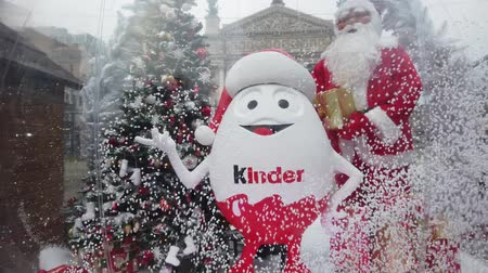Навидад : LVIV, UKRAINE - JANUARY 19, 2019: Christmas presents from kinder surprise in the city square. Christmas ball with Christmas tree, snow and gifts.