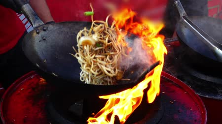 лапши : Asian cuisine. Cooking in a wok pan. Slow motion.