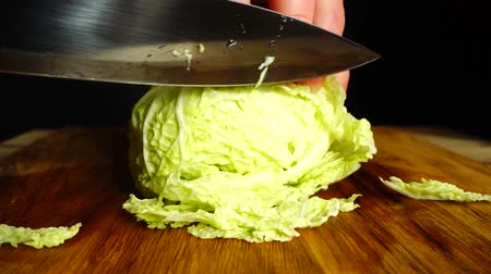 cuisine dark : The cook cuts the Napa cabbage with a knife. Slow motion.