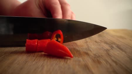 pimentas : The cook cuts hot chilli pepper. Slow motion.