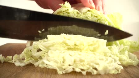 tábua de cortar : The cook cuts the Napa cabbage with a knife. Slow motion.