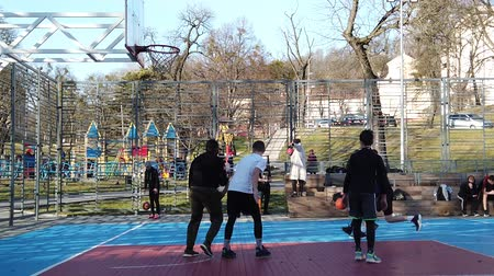 abroncs : LVIV, UKRAINE - FEBRUARY 22, 2020: Teenagers play basketball at the city sports ground in the public square. Stock mozgókép