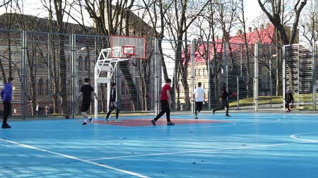 LVIV, UKRAINE - FEBRUARY 22, 2020: Teenagers play basketball at the city sports ground in the public square. Stock Footage