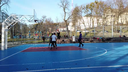 basketball : LVIV, UKRAINE - FEBRUARY 22, 2020: Teenagers play basketball at the city sports ground in the public square. Stock Footage