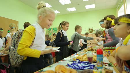 благотворительность : Charity fair, hungry buyer chooses cake in the gymnasium