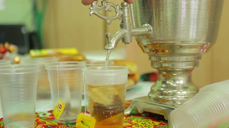 благотворительность : Charity fair, pour tea into cups from a samovar in the gymnasium