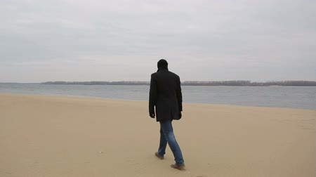 caminhada : Sad pensive man walks along the shore of the Volga River