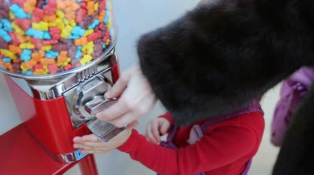 vending machine : Girl gets candy from machine sale of sweets in the mall