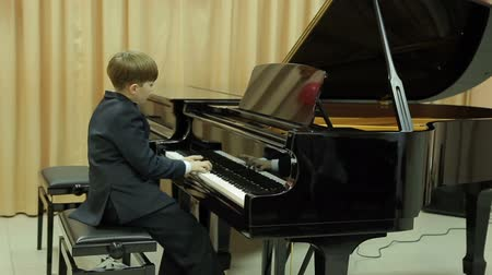 piyano : Boy playing the grand piano in the hall of the music school Stok Video