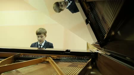 fortepian : Boy playing the grand piano in the hall of the music school, piano with the lid open