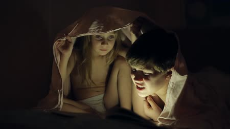irmãos : Boy reading a book to his sister lying under a sheet with a flashlight in the dark