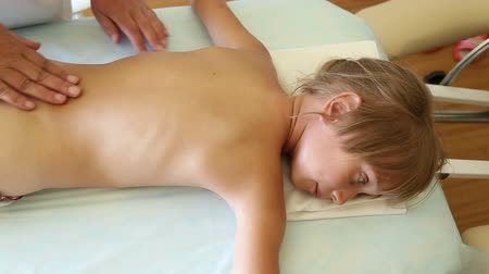 terapeuta : Woman massage therapist doing massage a little girl on massage bed in spa Wideo