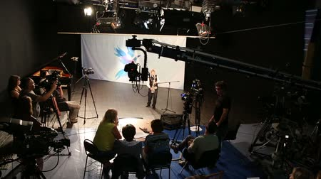 ator : Filming in a television studio, cameramen, directors and actor working Stock Footage
