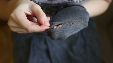delikleri : A woman sews up holes in socks, the symptom of poverty of a person