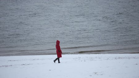 margem do rio : The girl in the red coat walks on the banks of the river Volga in Russia in winter Stock Footage