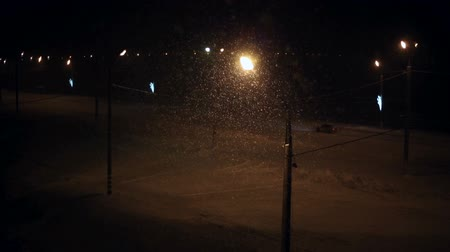 kar fırtınası : Snowfall at night, street lights shine, car going on the road