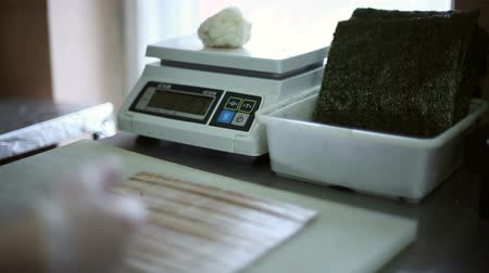 com escamas : A sushi chef prepares rolls, weighs on the scales a portion of rice and lays out the rice on a sheet of Nori seaweed Stock Footage