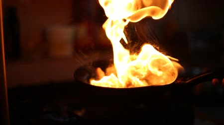 serpenyő : Chicken meat is fried in a frying pan on the gas stove and lights a fire