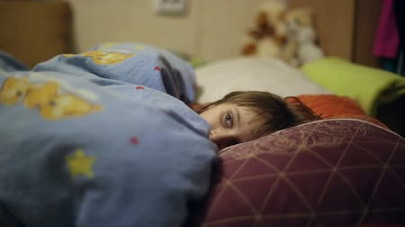 cobertor : The girl is lying in bed before going to sleep, she covered herself with a blanket and watches us